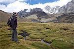 A trekker admires the escarpment view in the Cordillera Real, Andes Mountains, Bolivia, South America