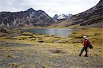 A trekker admires a laguna in the Cordillera Real, Andes Mountain, Bolivia, South America