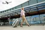 Mid femme adulte en tirant des bagages à l'aéroport