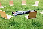 Homme d'affaires pose dans l'herbe entourée de chaises