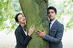 Business people hugging tree