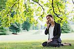 Femme d'affaires assis dans l'herbe, parlait au téléphone cellulaire