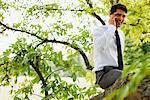 Homme d'affaires assis dans l'arborescence de conversation sur téléphone portable