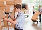 Homme d'affaires à l'aide de scanner sur boîte en entrepôt