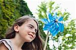 Smiling girl holding pinwheel outdoors