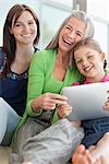 Grand-mère, mère et fille à l'aide de la tablette numérique