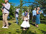 Famille dansant autour de « mai » dans le jardin