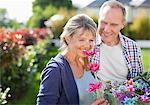 Senior couple smelling flowers in garden