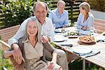 Portrait de sourire déjeuner enjoying de couple à table dans le jardin ensoleillé
