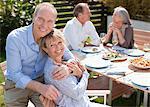 Portrait de sourire senior couple assis à table dans le jardin ensoleillé