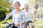 Portrait de couple senior sur les bicyclettes de sourire