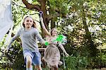 Mère et fille avec baguettes de bulle dans le parc