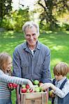 Grand-père et petits-enfants avec boisseau de pommes au verger