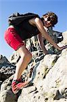 Hiker climbing boulder