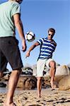 Men playing soccer on beach
