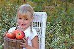 Little girl holding a basket of apples.