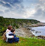 Children looking at coastal view of rocky Atlantic shore in Newfoundland, Canada