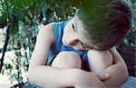 Boy resting head on knees, daydreaming