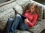 USA, Utah, Cedar Hills, Teenage girl (14-15) lying on sofa, using digital tablet