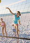 Preteen girls playing beach volleyball