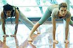Young adults doing prasarita padottanasana pose in yoga class