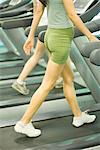 Deux femmes marchant sur le tapis de course, poitrine vers le bas