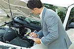 Homme d'âge mûr en costume inspection automobile