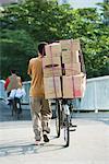 Homme qui marche avec vélo empilée avec boîtes