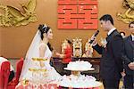 Mariée et le marié debout face à face, regardant les uns les autres, toilettent parlant dans le microphone
