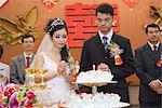Jeunes mariés, debout à côté de gâteau de mariage avec combustion bougie, yeux fermés, jointes mains