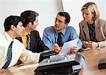 Trois hommes et une femme d'affaires examinant le document