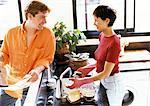 Mann und Frau in der Küche, Blick auf einander über Theke, Frau Geschirr spülen