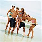 Teenagers on beach holding surfboard