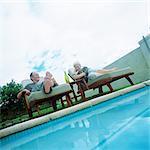 Mature Couple im Sessel neben Pool liegen
