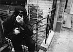 Masked man holding sub-machine gun, b&w