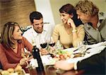 Gruppe junger Menschen um den Tisch, Wein trinken und lachen