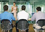 Frau steht vor drei Männer sitzen nebeneinander