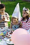 Fille de souffler les bougies sur le gâteau d'anniversaire à la fête d'anniversaire en plein air