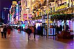 Fußgänger in der Nacht zu Fuß vorbei an Geschäften auf der Nanjing Road, Shanghai, China, Asien