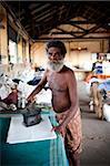 Man ironing in laundry, Cochin, Kerala, India, Asia