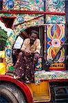Kerelan pilote assis dans la cabine du camion décorée de couleurs vives, Kerala, Inde, Asie