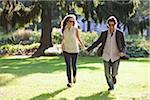 Young Couple Running through Park, Ontario, Canada