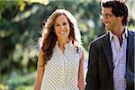 Close-up Portrait of Young Couple Walking through Park
