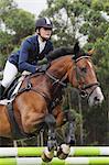 Junge weibliche Reiter springen Hürde