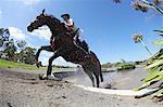 Reiter überqueren Wasser im Pferdesport-Ereignis