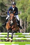 Young Woman Horseback Rider Jumping Hurdle