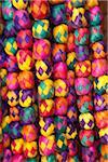 Woven straw garlands hanging in crafts market.