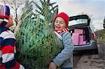 Two boys lifting Christmas tree to car