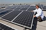 Ouvrier assis en dehors des panneaux solaires