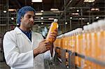 Worker examining orange juice bottle at bottling plant